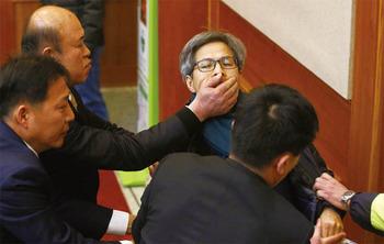 юриста Квон Ян Гука убирают из зала суда охранники, затыкая ему рот