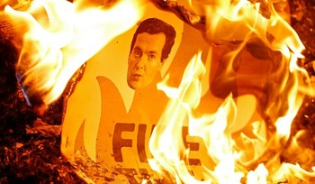 Плакат с портретом британского министра финансов Джорджа Осборна сгорает во врем